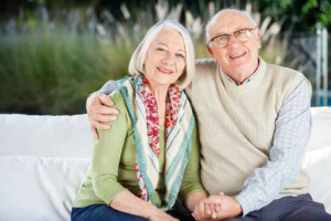 Happy Senior Man Sitting With Arm Around Woman On Couch